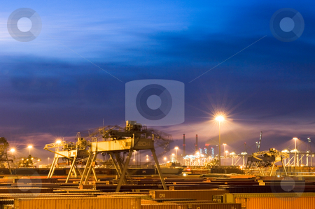 Moving containers stock photo, Night scene of a container terminal, with fully automated cranes moving through the vast rows of containers. by Corepics VOF