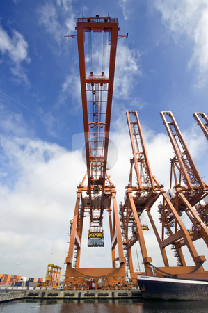 Cargo Crane stock photo, A huge cargo crane, carrying a container in an industrial harbor environment by Corepics VOF
