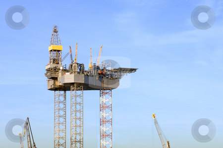 Oil rig construction stock photo, An oil rig is being constructed in a harbor area, to be towed to sea after completion. by Corepics VOF