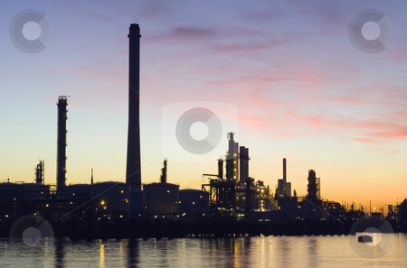 Oil Refinery at sunset stock photo, The silhouette of an oil refinery at sunset, against a radiant sky by Corepics VOF