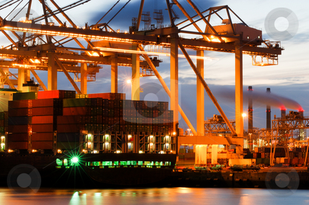 Container terminal activity stock photo, The motion and activity of a container terminal at dusk, with all fascets of the harbor: the ships, the containers, the cranes, the carriers, the processing industry. by Corepics VOF