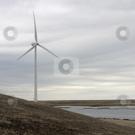 Wind turbine on an artificial dyke stock photo, The human reinforcement of the Dutch coast with it's concrete dykes provides the needed space for alternative energy sources, such as windturbines. by Corepics VOF