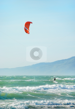 Kite Surfing in San Francisco stock photo, Surfer with red kite surfing off the beach in San Francisco, California on a sunny day. by Denis Radovanovic
