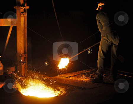 Cast iron factory stock photo, A man working in a cast iron factory close to the melting pit of the foundry by Corepics VOF