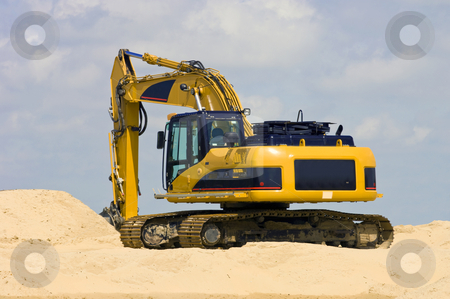 Digger stock photo, A Digger on top of a heap of sand by Corepics VOF