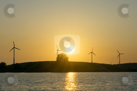 Green Energy stock photo, Four windmills lined up on a knoll in front of a blazing sunset by Corepics VOF