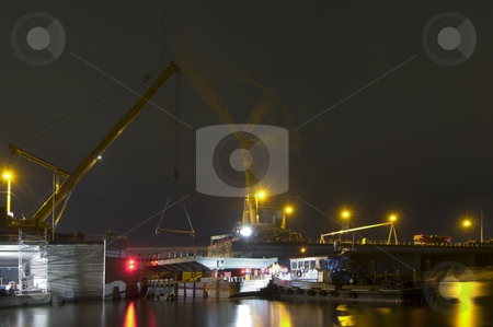 Motorway Bridge Replacement stock photo, Roadworks - replacing a bridge part over a canal continues throughout the night. Twoi cranes are about to lift the new part in place. The replacement bridge is held in place by a tugboat on a barge. The marking