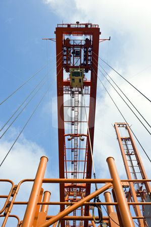 Container hoisting rig stock photo, The hoisting rig, used to haul containers at an industrial harbor, with the wires leading up to a huge crane by Corepics VOF