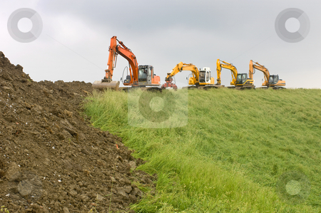 Reenforcement of a Dutch Dyke stock photo, Four diggers on top of a dyke, at the works to reenforce the Dutch coast line on a grey, rainy day. by Corepics VOF