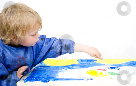 Painting with blue poster paint stock photo, A young boy painting with blue poster paint, reaching for a palette with his brush by Corepics VOF
