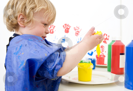 Messing with paint stock photo, Young boy dipping his hands in a pot of finger paint by Corepics VOF