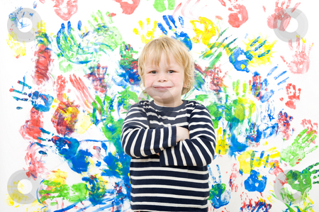 Proud looking boy stock photo, A proudly looking boy with his arms crossed after completing his work of art - finger painting on a wall by Corepics VOF