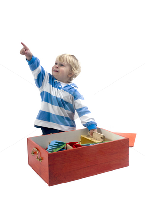 Playing boy stock photo, A 3 year old boy playing with a wooden train, and pointing by Corepics VOF