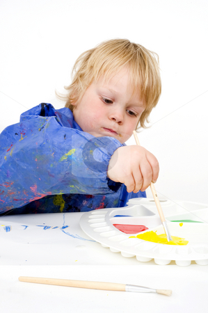 Reaching to get paint stock photo, A young boy, reaching to fill his brush with poster paint by Corepics VOF