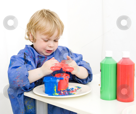 Playing with paint stock photo, Boy with an apron playing with various colors finger paint by Corepics VOF