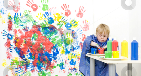 Getting finger paint stock photo, A young boy putting his hands in a pot with finger paint to get more red for his painting by Corepics VOF