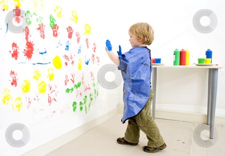 Boy ready to fingerpaint stock photo, Painter boy approaching the wall he's finger painting on by Corepics VOF