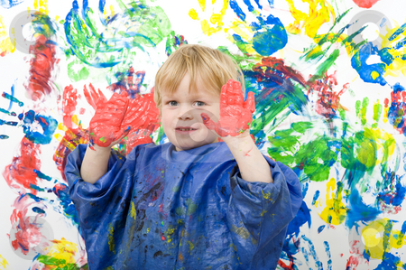 Hands with paint stock photo, Boy showing his hands covered with red finger paint in front of his work of art by Corepics VOF