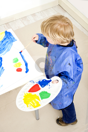 Painting a traffic light stock photo, A young boy, standing next to a table with a big sheet of paper on a cardboard surface with a palette with poster paint in his hands, painting a traffic light by Corepics VOF