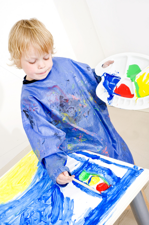 Poster painting stock photo, Young painter working on a painting with poster paint, coloring a traffic light by Corepics VOF