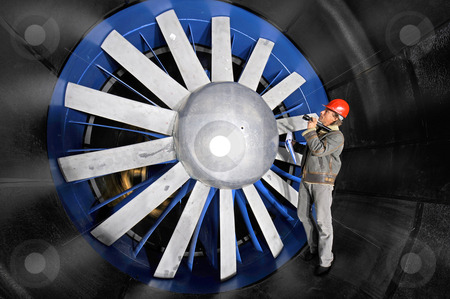 Inspecting a windtunnel stock photo, An engineer, wearing a red hardtop, inspecting a windtunnel from up close by Corepics VOF