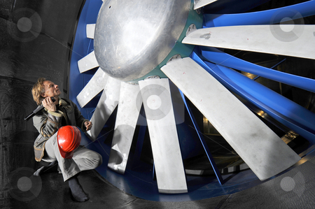 Inspecting the windtunnel stock photo, An engineer, with a hardtop on his knee and a flashlight in his hand, inspecting the huge rotor of an industrial windtunnel by Corepics VOF