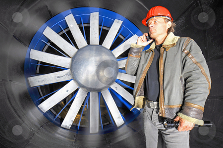Wind Tunnel Call stock photo, An engineer, holding a flashlight, calling from within a huge, industrial wind tunnel by Corepics VOF