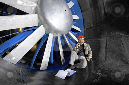Windtunnel engineer stock photo, An engineer, checking up on the mechanical structure inside a windtunnel by Corepics VOF