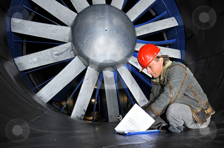Windtunnel engineer stock photo, An engineer, wearing a hardtop, going through his notes in front of a huge industrial windtunnel rotor by Corepics VOF
