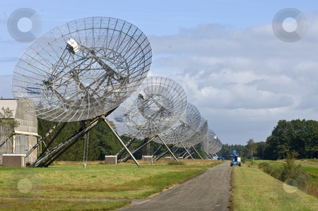 Eleven Radio Telescopes in a row stock photo, The Eleven Radio Telescopes, located in Westerbork, the Netherlands, in a row, with a maintenance cart near the odd one out. by Corepics VOF