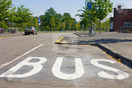 Bus stop stock photo, A bus stop with the marking BUS on the road in white letters by Corepics VOF