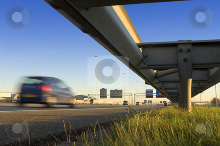 Motorway safety rail stock photo, A motorway safety rail with route information sign and motion blurred passing cars by Corepics VOF