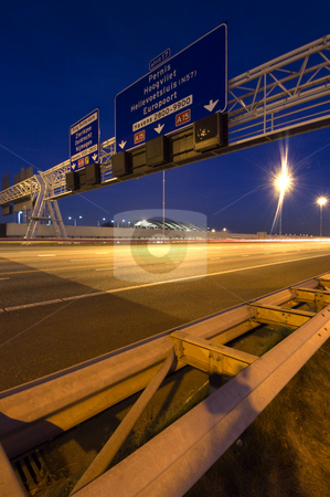 Overhead Motorway Information Signs stock photo, Steel structures, supporting traffic signs and direction information systems above a motorway at night by Corepics VOF