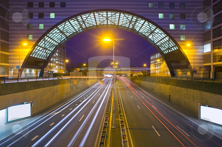 Inner city highway stock photo, An inner city highway at night with an office building, bridging the traffic by Corepics VOF
