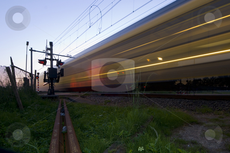 Passing train stock photo, A train passing a railway intersection at hight speed just after dusk by Corepics VOF