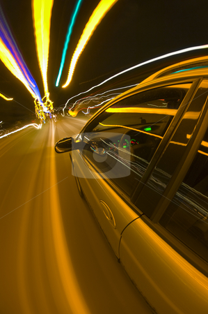 Night drive stock photo, A car speeding towards the horizon on an uneven road, surrounded by colorful lights overhead. by Corepics VOF