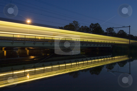Reflection of a passing train stock photo, The reflection of an intercity train on a bridge at night by Corepics VOF