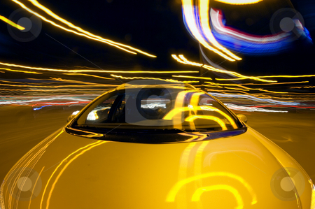 Taking a turn at night stock photo, A car taking a turn at night in a downtown environment by Corepics VOF