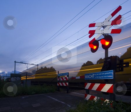 Passing train stock photo, A train passing a rail crossing, surrounded by fences and barb wire on a summer evening. by Corepics VOF