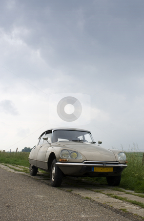 Vintage car on Dutch Dyke stock photo, A classic french car parked on the curb of a rural Dutch road on a dyke in Zeeland on a rainy day by Corepics VOF