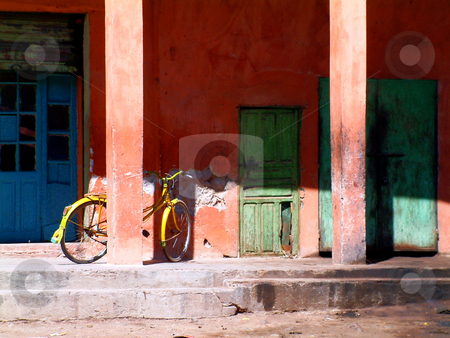 Old bike and primary faded colors stock photo, The old shop-front and the faded colors that once used to be bright and colorful by Corepics VOF