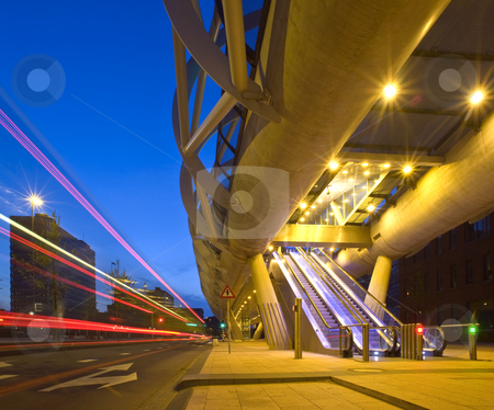 Public Transportation stock photo, A city bus driving past an elevated tram viaduct, with automated escalators leading up to the platform A stich of two images by Corepics VOF