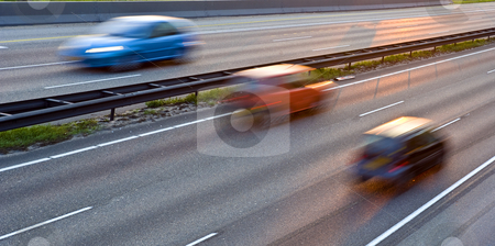 Heading Home stock photo, A multiple lane highway, with three cars in motion blur, driving in the evening light. by Corepics VOF