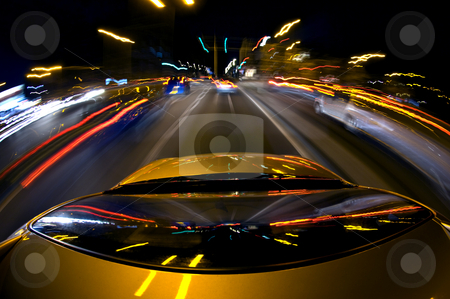 Downtown driving stock photo, A car, surrounded by blurred other cars due to the high speed, driving in a busy down town area with lots of lights, traffic and traffic lights by Corepics VOF