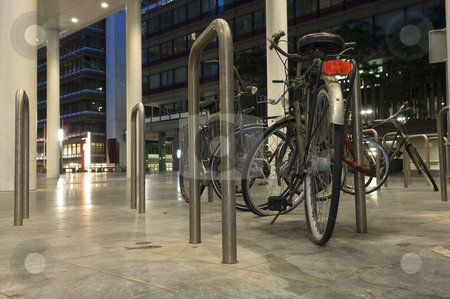 Bicicle parking stock photo, Bikes parked outside one of the ministries in the Hague, the Netherlands at night, one with a flat tire by Corepics VOF