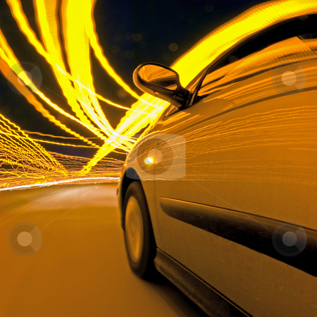 Night Drive stock photo, A car, driving through the clutter of lights at night by Corepics VOF