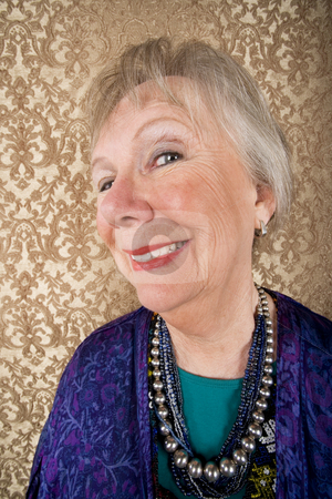 Smiling Senior Woman stock photo, Portrait of smiling senior woman in front of gold background by Scott Griessel