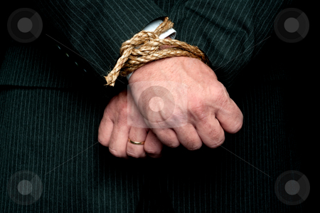A horizontal view of a business man with his hands tied infront  stock photo, A horizontal view of a business man with his hands tied infront of him. Concept: