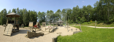 Playground panorama stock photo, A panorama of a large playground, made of natural materials, surrounded by trees by Corepics VOF