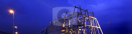 Construction site stock photo, A construction site at night, showing the steel profiled carcass and raw concrete, freshly erected walls by Corepics VOF